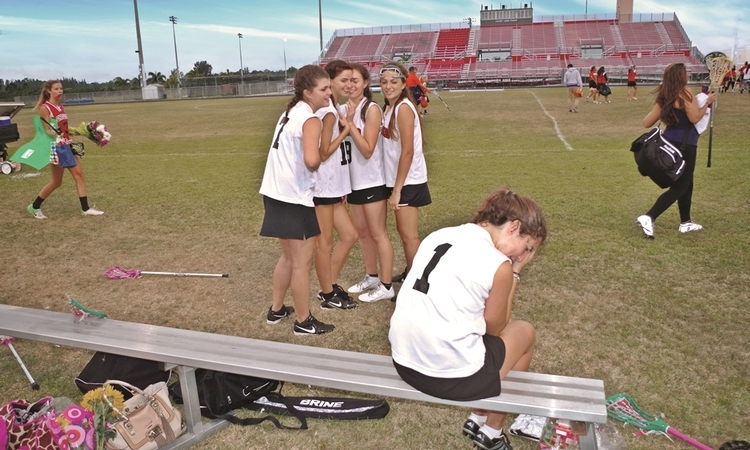 four girls bullying another girl while playing a sport